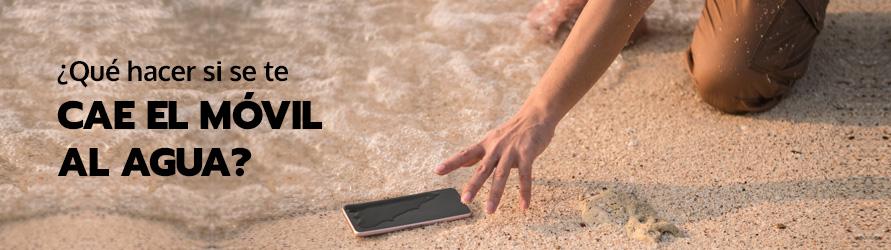 Una persona recoge de la orilla del mar un teléfono móvil